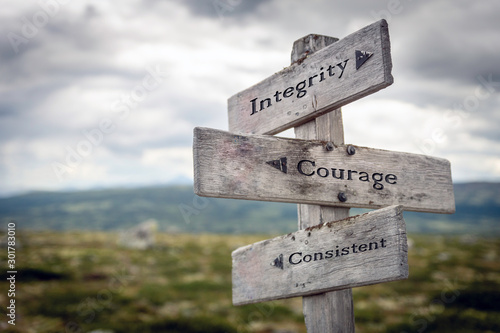 Integrity, courage and consistent text on wooden sign post outdoors in landscape scenery. Business, quotes and motivational theme concept.