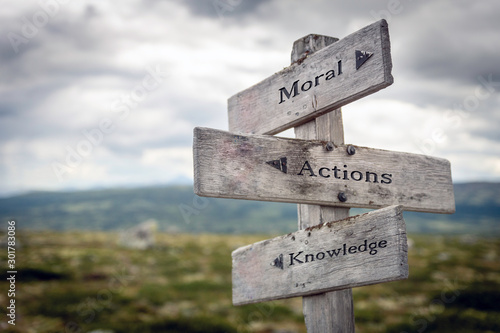 Moral, actions and knowledge text on wooden sign post outdoors in landscape scenery. Business, quotes and motivational theme concept.