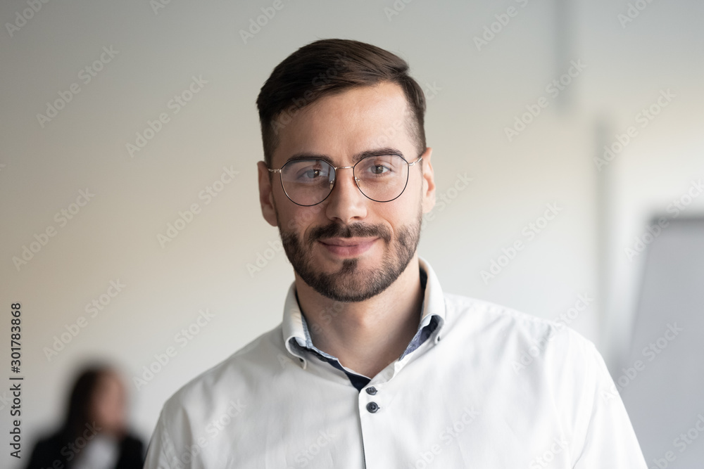 Fototapeta Portrait of millennial businessman posing looking at camera