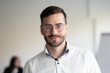 Portrait of millennial businessman posing looking at camera
