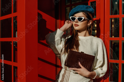 Slika na platnu Outdoor autumn fashion portrait of young elegant woman wearing stylish  denim beret, sunglasses, white sweater, holding brown textured crocodile leather bag, posing in red call box