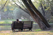 A Pair Of Lovers Sitting On Wooden Bench In Park Under Sunshine. Lake Water And Trees Around