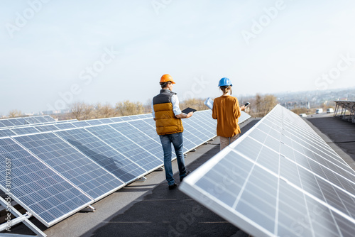 Fototapeta View on the rooftop solar power plant with two engineers walking and examining photovoltaic panels. Concept of alternative energy and its service obraz