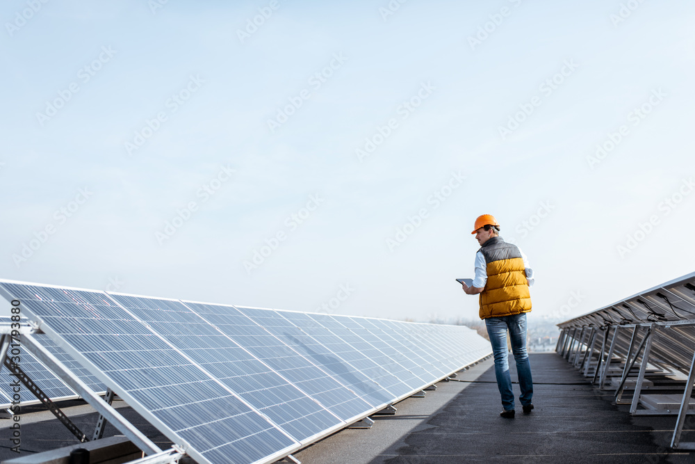 Fototapety, obrazy: View on the rooftop solar power plant with mann walking and examining photovoltaic panels. Concept of alternative energy and its service