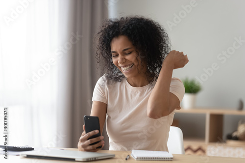 Fotografía  Happy African American woman using phone, celebrating success