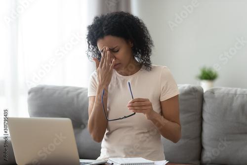 Billede på lærred Exhausted African American woman taking off glasses, dry eye syndrome