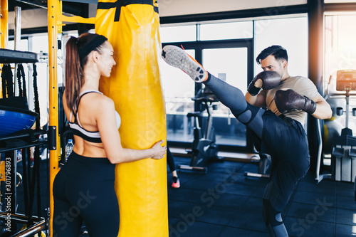 Obraz na plátne Young attractive woman with instructor on kickboxing training