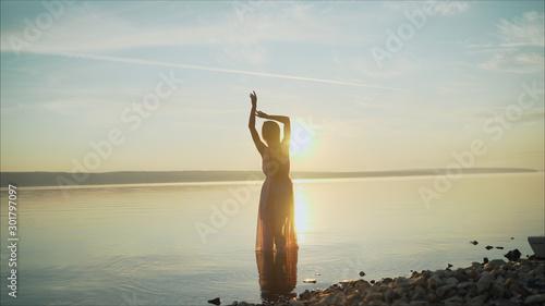 Obraz silhouette of a dancing girl on a background sunset. beautiful girl dancing and having fun outdoors. Girl dancing at dawn - fototapety do salonu