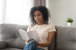 Leinwanddruck Bild - Focused serious African American woman reading book at home