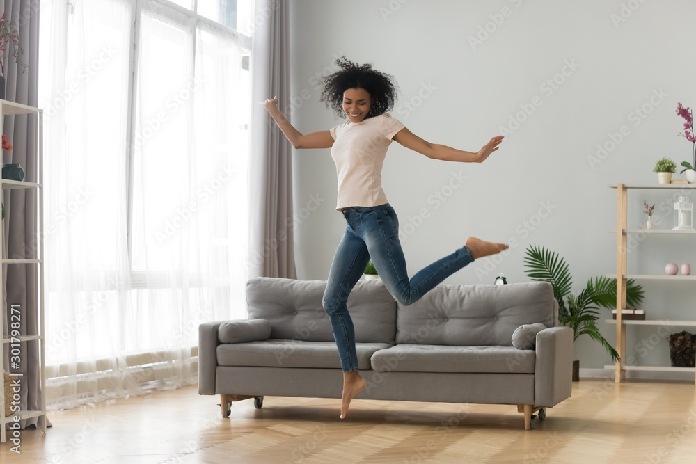 Fototapety, obrazy: Happy African American woman jumping in living room, celebrating success