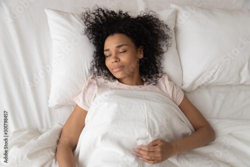Fototapeta Serene African American woman sleeping in comfortable bed top view