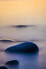 Fototapeta na wymiar Sunset at dusk at the beach along the rocky beach coast.