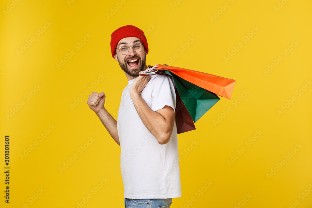 Fototapeta Bearded man with shopping bags with happy feeling isolated on yellow bacground