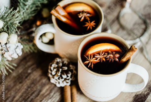 Mulled wine in white rustic mugs with spices, cinnamon and slide citrus fruit.Traditional hot drink in Christmas celebration party time.