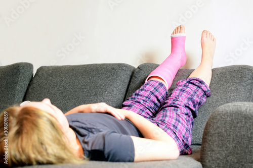 Pinturas sobre lienzo  Unrecognizable woman with orthopedic cast lies on sofa and has lifted her legs up