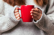 canvas print picture - Picture of a woman's hand holding a red coffee mug
