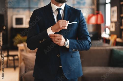 Fototapeta Handsome businessman adjusting his sleeves while standing in modern office