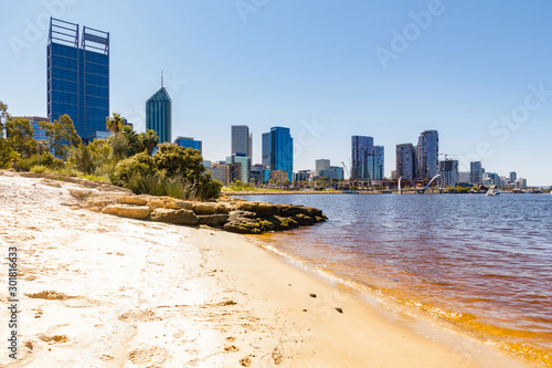 A beach scene on Swan River with the iconic skyscrapers of Perth, Western Australia, in the background on a sunny summer day