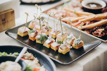 Delicious Food Table At Wedding Reception. Fish Finger Appetizers With Onion On Table At Wedding Or Christmas Feast. Luxury Catering Concept