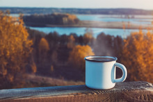 Enameled Cup Of Coffee Or Tea On Autumn Landscape Outdoors.