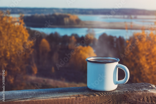 Foto auf Leinwand Schokobraun Enameled cup of coffee or tea on autumn landscape outdoors.