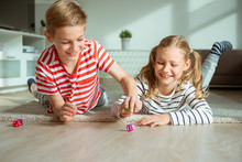 Portrait Of Two Cheerful Children Laying On The Floor And Playing With Colorful Dices