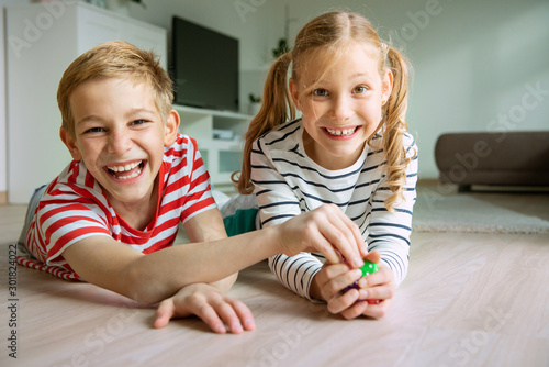 Obraz Portrait of two cheerful children laying on the floor and playing with colorful dices - fototapety do salonu