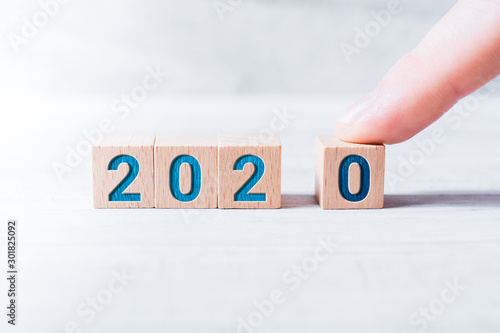Pinturas sobre lienzo  The Year 2020 Formed By Wooden Blocks And Arranged By A Male Finger On A White T