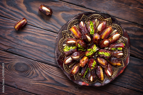 Fotomural  Dried dates stuffed with candied fruits and nuts on a rustic wooden table
