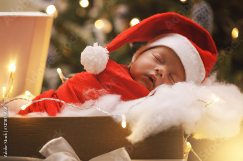 Photo  Cute newborn baby wearing Santa Claus hat is sleeping in the Christmas gift box