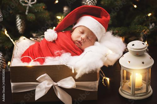 Fotografiet  Cute newborn baby wearing Santa Claus hat is sleeping in the Christmas gift box