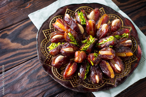 Cuadros en Lienzo  Dried dates stuffed with candied fruits and nuts on a rustic wooden table with copy space