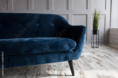 Corduroy sofa in a trendy loft interior in blue. Daylight sunlight.