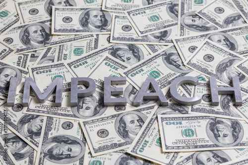 The word IMPEACH laid with aluminium letters on the US dollar banknotes backgrou Canvas Print