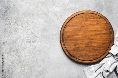 Fotografia, Obraz Round wooden pizza board on grey concrete background and grey linen textile