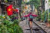 Fototapeta Uliczki - Woman walking on the railway in Hanoi, Vietnam