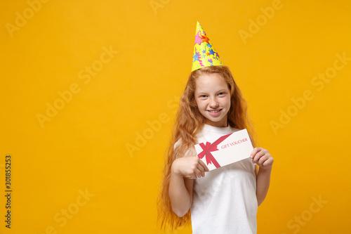 Fotografija  Smiling little ginger kid girl 12-13 years old in white t-shirt, birthday hat isolated on yellow background children portrait