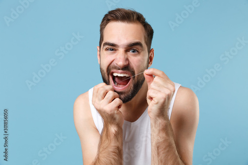 Bearded young man 20s years old in white shirt hold using dental floss isolated on blue pastel wall background studio portrait Obraz na płótnie