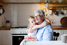 Child Is Giving Gift Box To Grandmother. Kid And Senior Woman Are Hugging In Cozy Home Kitchen. Happy Family Is Enjoying Kindness. Lifestyle Moment. Concept Of Holidays Hanukkah, Christmas, Birthday.