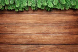 Fototapeta Kawa jest smaczna - green branches of a fir tree on wooden planks background, christmas frame with copy space