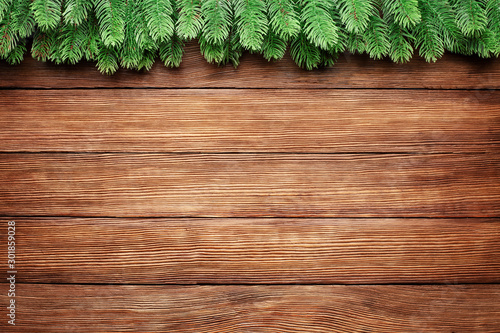 green branches of a fir tree on wooden planks background, christmas frame with copy space