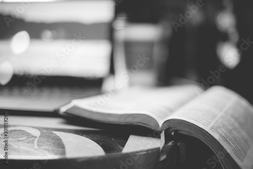 Fotografía Grayscale closeup shot of an open bible on the table wit ha blurred background