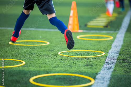 Fotomural  Selective focus to kid soccer player Jogging and jump at ring ladder marker on green artificial turf