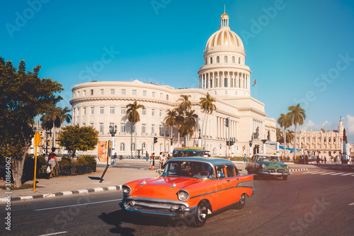 Photo Vintage cars next to the iconic Capitol building in Havana