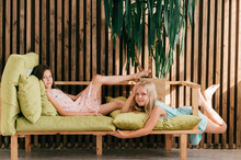 Two Beautiful Model Girls Lying On Bed In Interior Studio And Posing For Camera With Face Expression