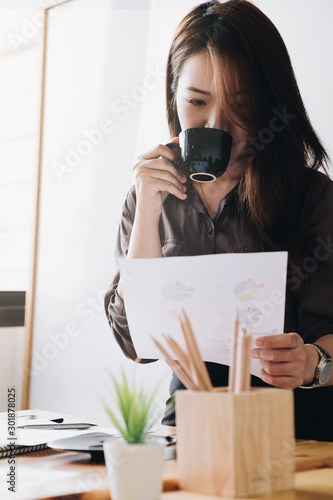 Businesswoman drinking cup of coffee before working on Monday morning. - 301878025