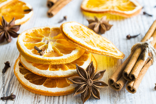 Photo Christmas spices - cinnamon sticks, star anise, cloves and slices of dried orange on old wooden background