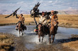 canvas print picture - A group of traditional kazakh eagle hunters holding their golden eagles on horseback while galloping through a river. Ulgii, Mongolia.