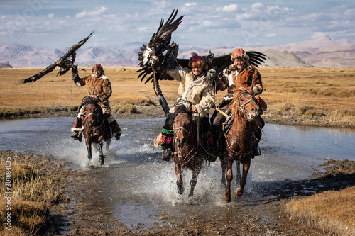 Fototapeta A group of traditional kazakh eagle hunters holding their golden eagles on horseback while galloping through a river