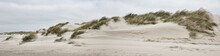 Panorama Of A Hill Covered In Grass In The Middle Of A Sandy Beach